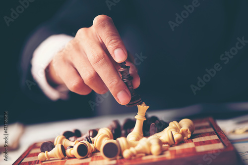 Fotografering Midsection Of Man Holding Chess Piece Over Board On Table