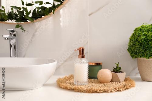 Fototapeta Soap dispenser, plants and candle near vessel sink in bathroom obraz