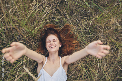 Fototapeta happy woman in haystack stretches hands up and cropped view