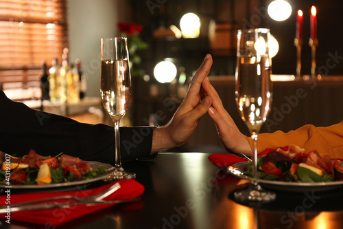 Fototapeta Couple holding hands together at table during romantic dinner in restaurant, closeup obraz
