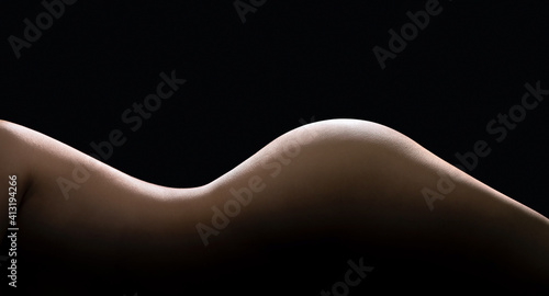 Obraz Female body curves in dark. Sexy shape and figure of a beautiful nude woman. Slim waist and perfect skin. Hot erotic naked model. Side torso, hips and buttocks. Low key silhouette on black background. - fototapety do salonu