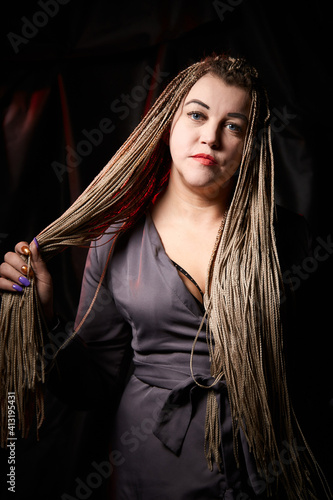 Photo Portrait of a blonde girl with a lot of pigtails on a black background in the st