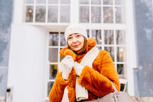 Smiling Modern Mature Woman In White Mittens,knitted Hat And Faux Fur Coat Outdoors In The City In Winter Firozi Day. Female Wrap In And Holding Scarf, Smiling, Looking At Camera.