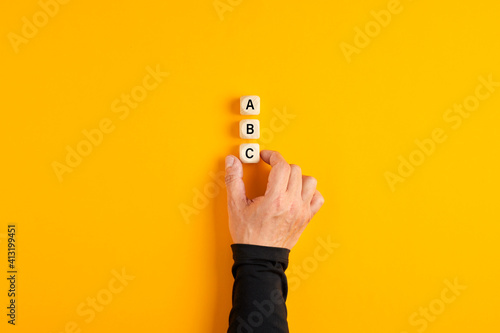 Male hand placing three wooden blocks with the letters of a b and c on yellow background.
