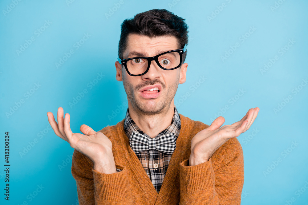 Fototapeta Photo of unhappy puzzled young man raise hands wear glasses bad mood isolated on pastel blue color background