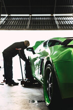 Mechanic Changing The Wheels Of A High-end Super Sports Car. Auto Mechanic Working In Garage. Repair Service.