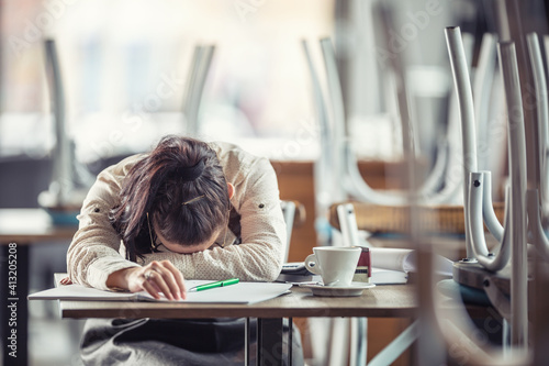 Exhausted female business owner rests her head on the table after piles of paperwork done in the bar after hours