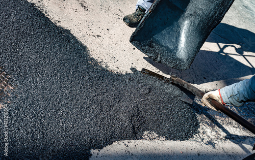 worker leveling fresh asphalt during asphalt pavement repair or construction wor Wallpaper Mural