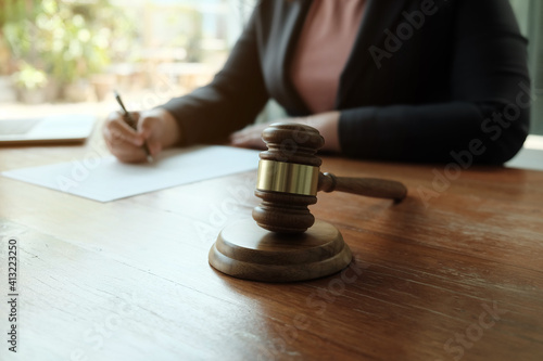 Obraz na płótnie Midsection Of Female Lawyer Writing On Document At Table In Office