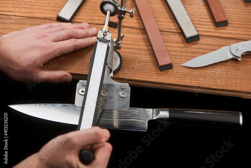 Papel de parede Hands sharpening a Japanese knife with Damascus steel using a manual machine