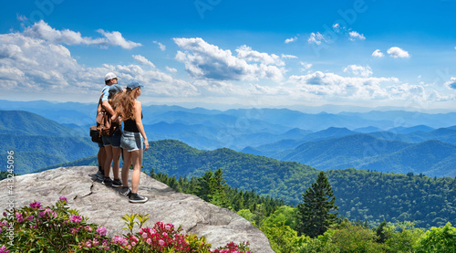Fotografie, Obraz Family standing with arms around on top of mountain, looking at beautiful summer mountain landscape
