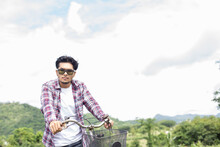 Portrait Of Young Man Wearing Sunglasses Riding Bicycle Against Cloudy Sky