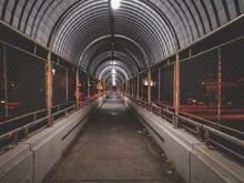 Diminishing Perspective Of Empty Footbridge At Night