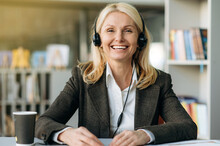 Webcam Portrait Of Successful Joyful Female Consultant In Headset At The Workplace. Happy Senior Adult Business Lady In Stylish Suit Sit At The Desk, Communicate With Colleagues On Video Conference