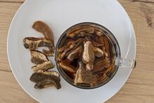Piatto E Tazza Di Vetro Con Funghi Porcini Secchi In Ammollo Vista Dall'alto