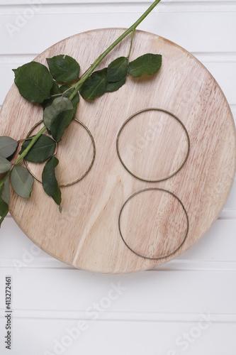 Fototapeta Łodyga róży zielona na okrągłej jasnej desce obraz