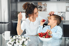 The Boy Eats Strawberries With His Mother At Home In The Kitchen. Happy Mom And Son Spend Time Together