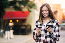 Girl Holding Credit Card Using Smartphone For Online Shopping, Mobile Banking. Young Freelancer Gets Paid, Checks Balance. Woman Orders Food Online, Book Tickets