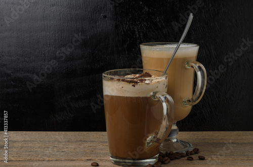 Canvas Print Two glass cups with a cappuccino and an iced chocolate on a wooden table with a