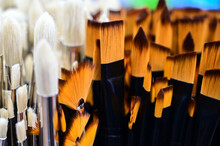Stunning And Sophisticated Paint Brushes In The Shop. Natural Squirrel Brushes Of Different Forms And Sizes. Artist's Tools On The Blurred Background. Black And White Brushes.