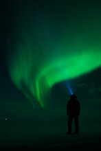 Man Standing Watching Aurora Borealis, Northern Lights Witch Head Torch In North Iceland, Europe