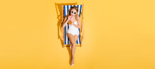 Top View Of Woman In Swimsuit And Sunglasses Drinking Refreshing Cocktail In Deck Chair On Yellow, Banner.