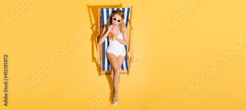Foto top view of woman in swimsuit and sunglasses drinking refreshing cocktail in deck chair on yellow, banner