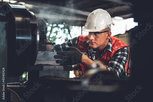 Fototapeta Smart factory worker or engineer do machine job in a manufacturing workshop