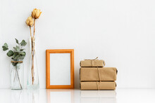 Wooden Photo Frame And Dried Plants In Vases On A White Background. Minimalistic, Gentle Summer Layout. Blank For A Postcard. Interior For Design.
