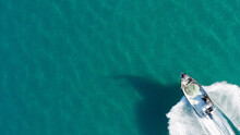 Small Fishing Boat Roaring Across Calm Smooth Sea, Aerial View.