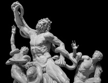 Front View Of Famous Laocoon Roman Copy Sculpture Isolated On Black Background. Trojan Laocoon Was Strangled By Sea Snakes With His Two Sons