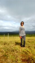 Young Woman Wearing Sunglasses While Standing On Grassy Field Against Cloudy Sky