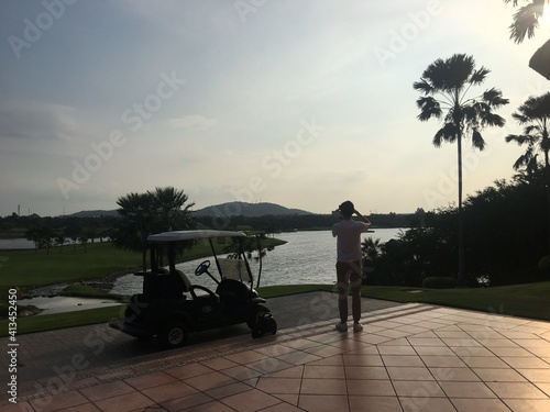 Fotografia, Obraz Rear View Of Mid Adult Man Standing On Footpath By Lake Against Sky During Sunse