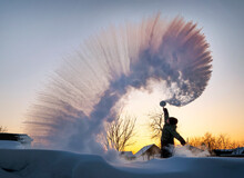 Guy Splashes Boiled Water From A Thermos Over His Head Against The Backdrop Of A Sunset In Frosty Weather. The Effect Of Instant Freezing Of Hot Water In Severe Frost. Siberian Fireworks Experiment