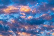 Beautiful Clouds In Blue Sky, Illuminated By Rays Of Sun At Colorful Sunset To Change Weather. Soft Focus, Motion Blur Summer Cloudscape Background.