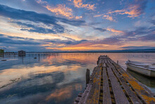 Amazing Mood Sunset At A Lake Coast With A Boat At A Wooden Pier