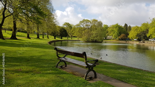 Canvas Print Empty Bench In Park By Lake Against Sky