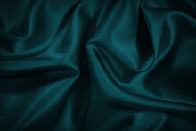 Black Blue Green Abstract Background. Dark Green Silk Satin Texture Background. Beautiful Wavy Soft Folds On The Surface Of The Fabric. Teal Elegant Background With Copy Space For Design. Web Banner.
