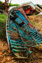 Abandoned Boats On Mud Against Sky