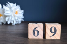 Number 69, Rating, Award, Empty Cover Design In Natural Concept With A Number Cube And Peony Flower On Wooden Table For A Background.