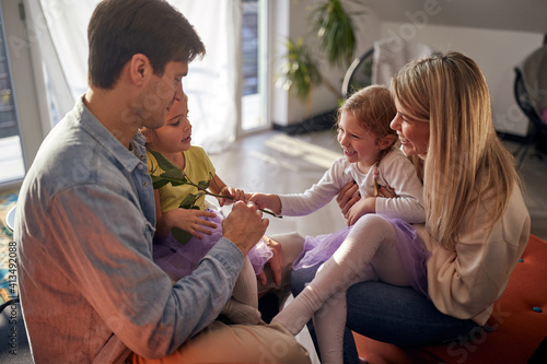 Obraz Caucasian parents playing together with their children - fototapety do salonu