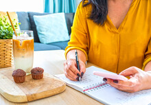 Cropped Shot Of Young Business Female In Yellow Shirt Writing Short Note And Holding Smartphone Sitting With Iced Coffee And Muffins Comfortable Working From Home Near The Windows.