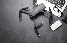 Modern Drone With Video Camera And Laptop On Grey Stone Table, Flat Lay. Space For Text