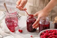 Woman With Jars Of Sweet Raspberry Jam