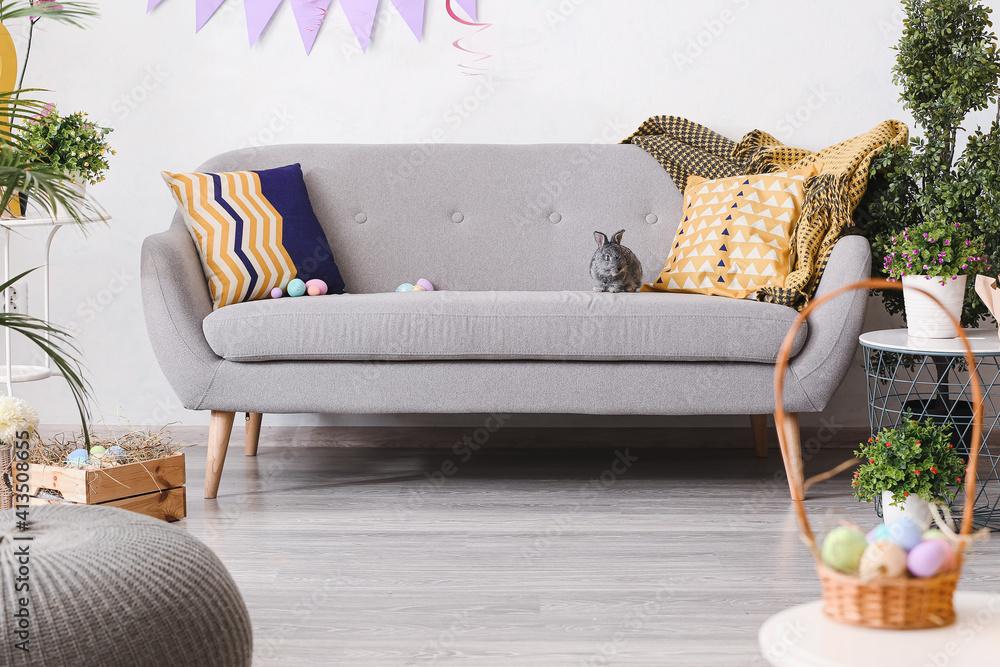 Fototapeta Cute rabbit and Easter eggs on sofa in room