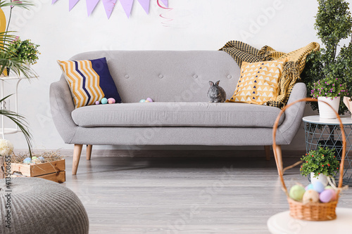 Fototapeta Cute rabbit and Easter eggs on sofa in room obraz