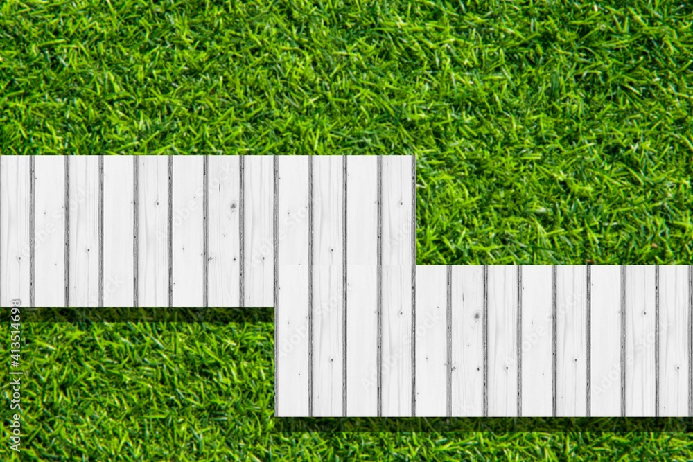 Fototapeta Top view of a white wooden walkway in a green lawn