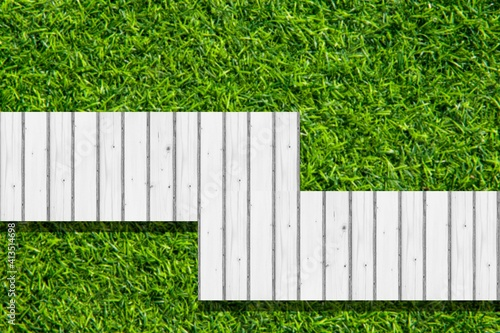 Top view of a white wooden walkway in a green lawn