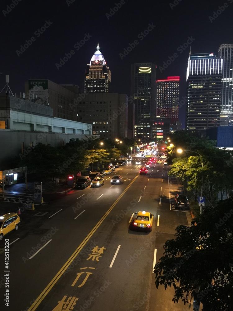 Fototapeta Traffic On City Street And Buildings At Night