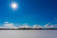 Agricultural Land In Winter In Germany Covered With Snow Soil,bright Sun In The Blue Sky , Few Clouds